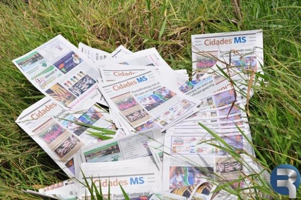 Jornal impresso é jogado em meio ao matagal atrás da estação ferroviária